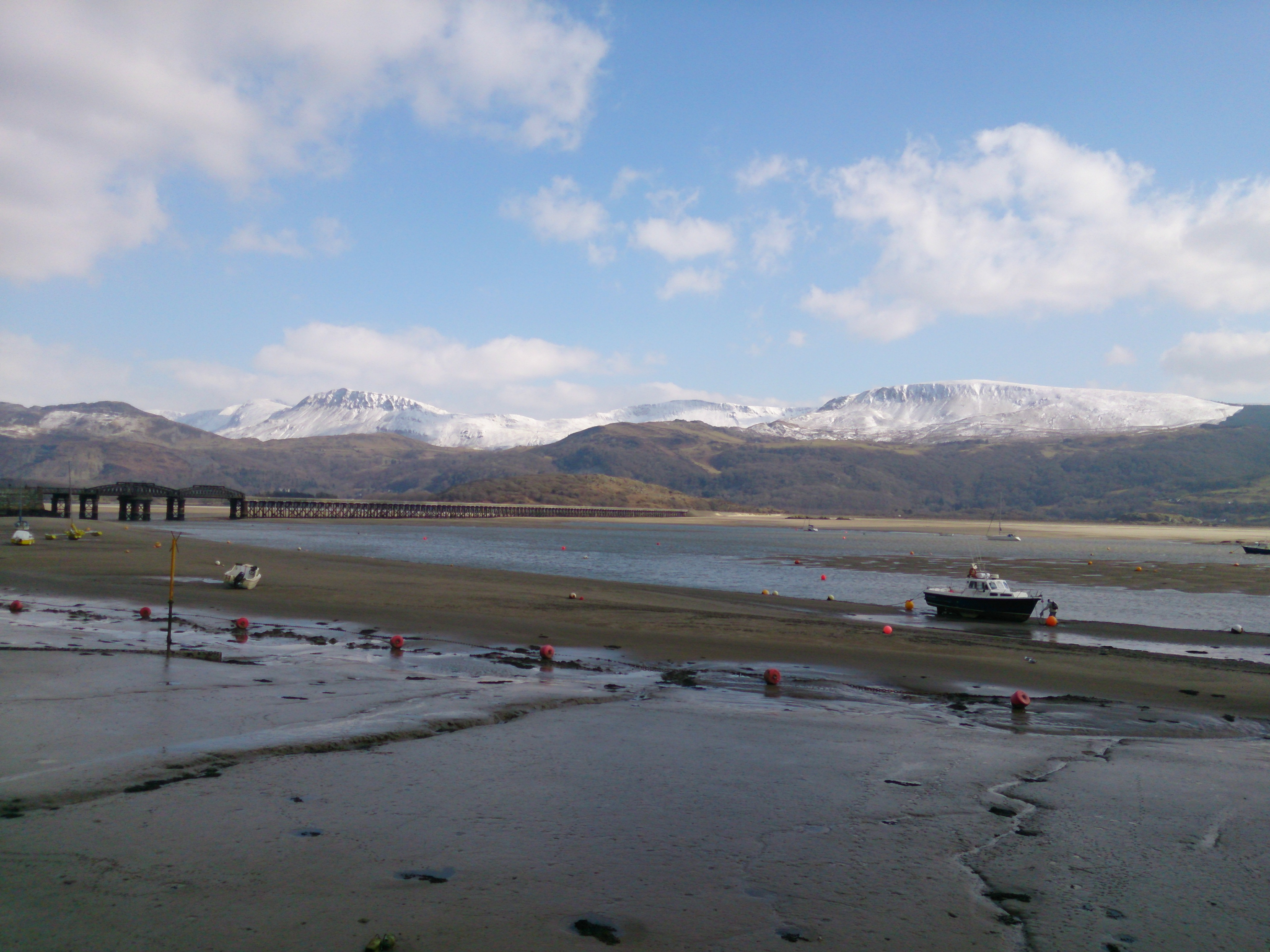 Barmouth harbour at low tide showing the snow capped mountains.